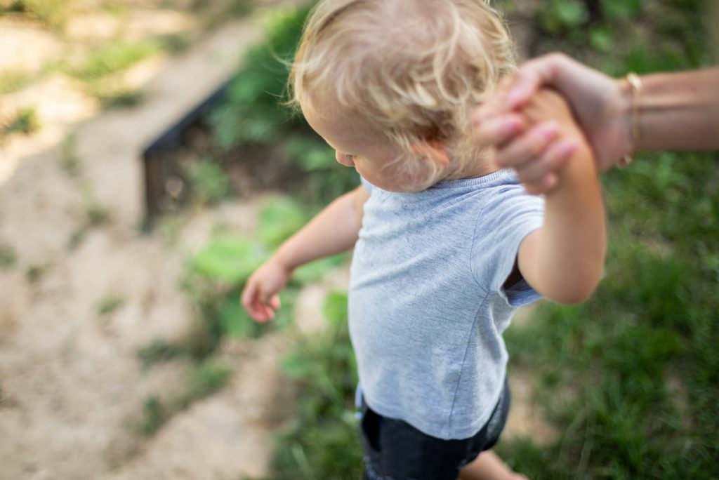 Parent holds hand of small child while walk outdoor